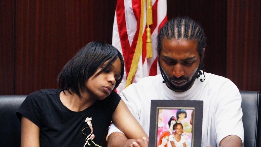 FILE -- In this May 18, 2010 file photo, Dominika Stanley and Charles Jones hold a photo of their 7-year-old daughter Aiyana Jones in an attorney's office in Southfield, Mich. Aiyana was killed while she slept on a couch by a Detroit police officer accused of handling his gun recklessly during a frantic search for a murder suspect in 2010. (AP Photo/Carlos Osorio, File)
