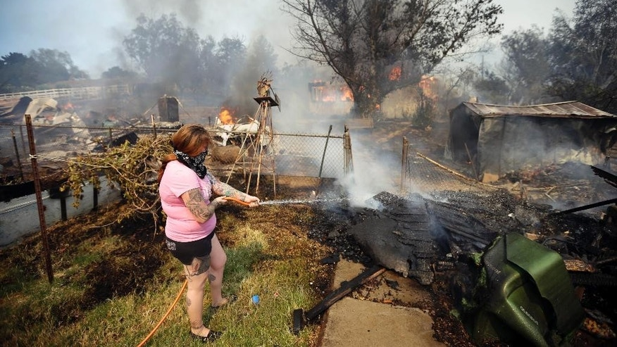 FILE - In this May 15, 2014 file photo, a woman douses around her home with water from a hose as her neighbor's home burns during a wildfire in Escondido, Calif. Fire-hardened Southern Californians know that when the Santa Ana winds blow, a wildfire probably isn't very far behind, the only questions are where and how bad it will be. The U.S. Forest Service on Wednesday, Sept. 17, 2014, rolled out a mapping tool that should help homeowners and first responders get a better idea of just where those fires are most likely to erupt during a Santa Ana wind event. (AP Photo/Gregory Bull, File)