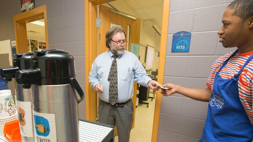 After paying his dollar for a hot cup of coffee to Workplace Readiness student Jerome Anderson, teacher Tom Lewis gets his morning coffee at Marietta High School.