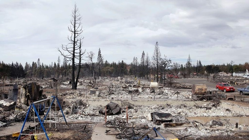The remains of houses destroyed by fire sit in Weed, Calif., Tuesday, Sept. 16, 2014. In just a few hours Monday, wind-driven flames destroyed or damaged roughly 100 homes, the saw mill and a church in Weed. (AP Photo/Rich Pedroncelli)