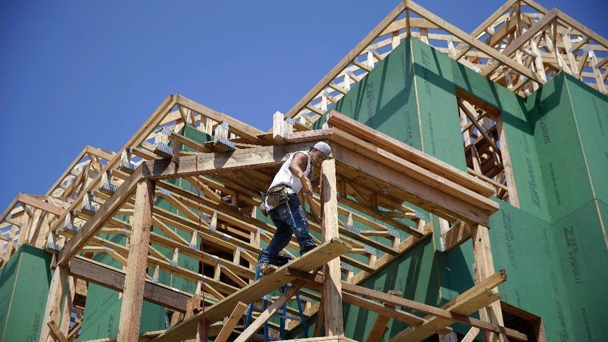 In this Wednesday, July 30, 2014 photograph, a builder works on the construction of new homes in Belmar, N.J. The Commerce Department reports on U.S. home construction in August on Thursday, Sept. 18, 2014. (AP Photo/Mel Evans)
