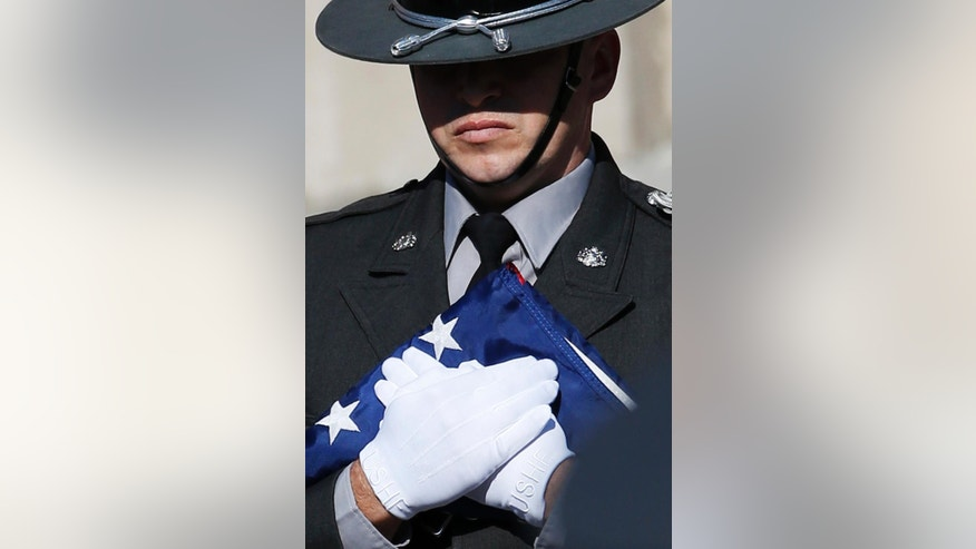 A law enforcement officers holds a folded United States flag before a funeral service for Pennsylvania State Trooper Cpl. Bryon Dickson, Thursday, Sept. 18, 2014, in Scranton, Pa. Dickson was killed on Friday night in an ambush shooting at the state police barracks in Blooming Grove Township. Authorities are looking for 31-year-old Eric Frein, of Canadensis, who has been charged with killing one trooper and wounding another outside the barracks. (AP Photo/Matt Slocum)