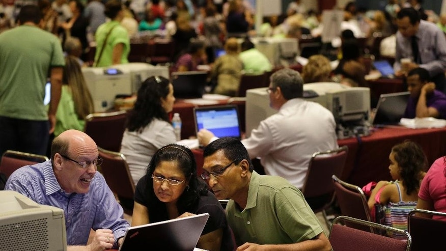 FILE - In this Sept. 3, 2014 file photo, former Revel Hotel Casino employees, Jignasha Shah, 45, center, and Ranjitsinh Rana, 56, right, get help from John McCaffery, as they and thousands of other newly laid-off casino workers file for unemployment benefits at the Atlantic City Convention Center in Atlantic City, N.J. The government reports on state unemployment rates for August on Friday, Sept. 19, 2014. (AP Photo/Mel Evans, File)