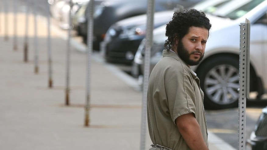 FILE - In this Monday, June 2, 2014, file photo, Mufid Elfgeeh is taken from his arraignment in federal court  in Rochester, N.Y. Elfgeeh, a 30-year-old naturalized U.S. citizen in Rochester, was arrested in May after he bought two handguns and a pair of silencers that federal officials said he planned to use to kill U.S. veterans of Iraq fighting and Shiites living in the Rochester area. (AP Photo/Democrat & Chronicle, Shawn Dowd, File) MANDATORY CREDIT; MAGS OUT; NO SALES