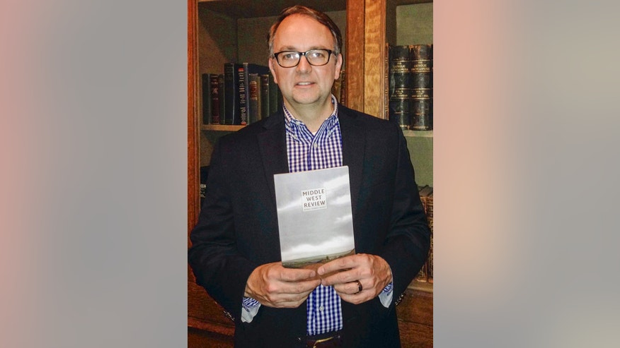 In this photo from Sept. 17, 2014, which was provided by Rachel Bohlmann, Director of Continuing Education at the Newberry Library, Jon Lauck, chairman of the Midwest History Working Group poses in Chicago with a copy of the Middle West Review. (AP Photo/The Newberry Library, Rachel Bohlmann)