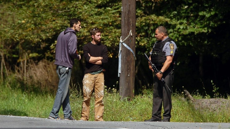 Residents talk with a Pennsylvania State Police Trooper on the corner of Route 447 and Bear Town Road in Barrett Township on Saturday, Sept. 20, 2014, near Canadensis, Pa., during a search for suspected killer Eric Frein. Frein is suspected of fatally shooting a state trooper and wounding another at the Blooming Grove state police barracks a week earlier. (AP Photo/Scranton Times & Tribune, Butch Comegys)