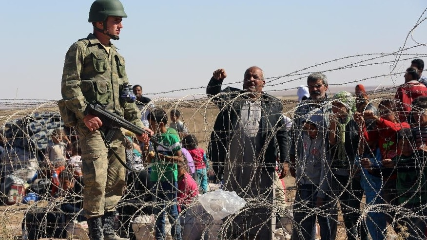A Turkish soldier stands guard as several hundred Syrian refugees wait to cross the border in Suruc, Turkey, Sunday, Sept. 21, 2014. Turkey opened its border Saturday to allow in up to 60,000 people who massed on the Turkey-Syria border, fleeing the Islamic militants' advance on Kobani.  (AP Photo/Burhan Ozbilici)