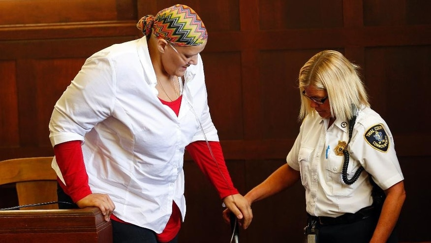 Tanya Singleton is helped down from the stand by a court officer in Suffolk Superior Court, Tuesday, Sept. 23, 2014, in Boston, after she pleading guilty to contempt for refusing to testify before a grand jury that indicted her cousin, former New England Patriots football player Aaron Hernandez, in the 2012 killings of two Boston men. She was sentenced to two years of probation. (AP Photo/The Boston Globe, Jessica Rinaldi, Pool)
