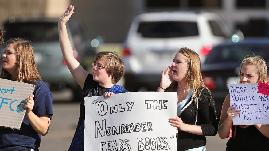 High school students Bronwyn Elisha, center left, and Tori Leu, center right, cheer as a passing motorist honk in support of their protest against a Jefferson County School Board proposal to emphasize patriotism and downplay civil unrest in the teaching of U.S. history, at Ralston Valley High School, in Arvada, Colo., Tuesday, Sept. 23, 2014. Students from at least two high schools walked out of class Tuesday in the second straight day of protests in Jefferson County. (AP Photo/Brennan Linsley)