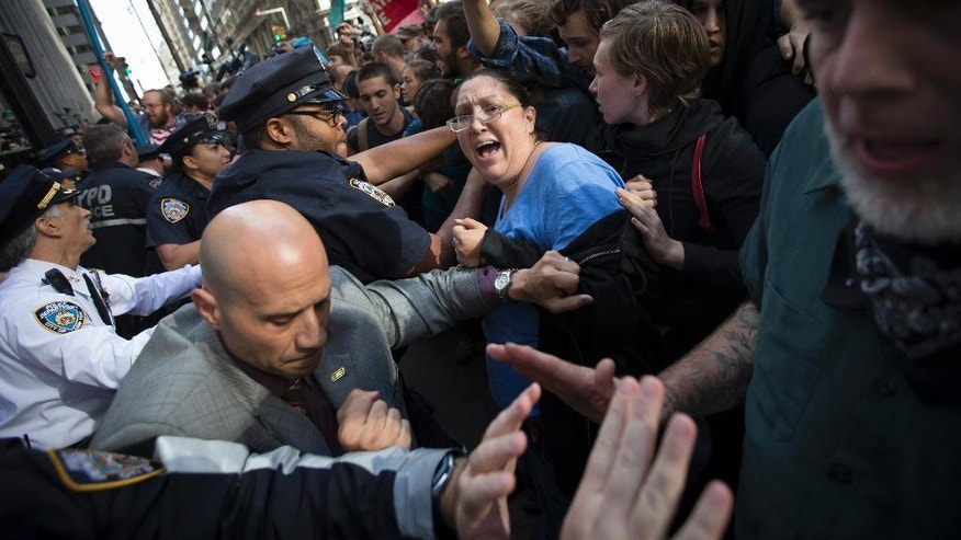 A demonstrator screams as protestors and police wrestle near a barricade on the corner of Wall Street and Broadway during a march demanding action on climate change and corporate greed, Monday, Sept. 22, 2014, a day after a huge climate march in New York. (AP Photo/John Minchillo)