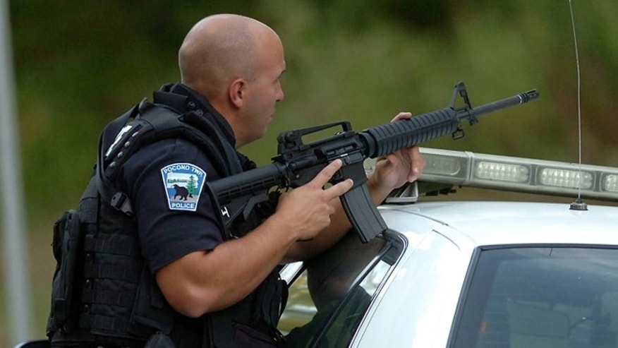 SEPT. 21: A Pocono Township Police patrolman has his weapon ready on Route 447 in Price Township near Canadensis, Pa., during a massive search for suspected killer Eric Frein.