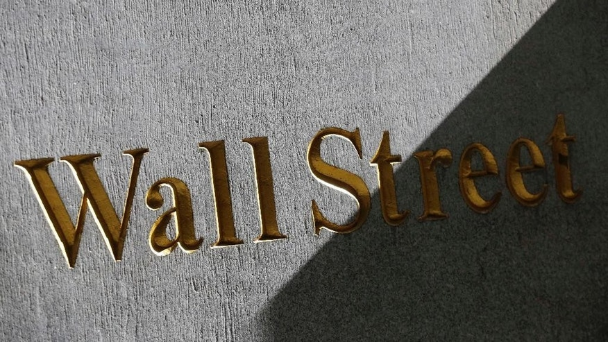 FILE - This March 4, 2013 file photo shows a sign for Wall Street on the side of building near the New York Stock Exchange, in New York. U.S. stocks are opening lower Tuesday, Sept. 23, 2014, following disappointing economic news and U.S.-led airstrikes against Islamic State militants in Syria. (AP Photo/Mark Lennihan, File)