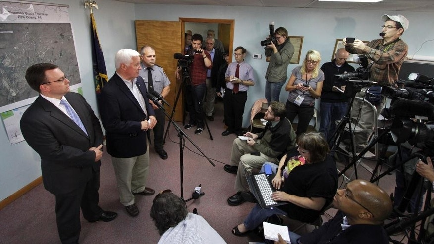Pennsylvania Gov. Tom Corbett speaks of accused cop killer Eric Matthew Frein during a news conference at Blooming Grove Municipal Township Building in Blooming Grove Township, Pa., Monday, Sept. 22, 2014. At left is Pike County District Attorney Ray Tonkin and at right is Pennsylvania State Police Lt. Col. George Bivens. (AP Photo/Scranton Times-Tribune, Michael J. Mullen)
