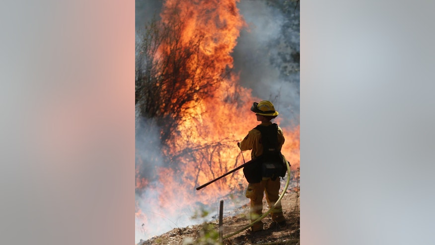 Flames from a controlled burn engulf a hillside as a firefighter watches while fighting the King Fire on Tuesday, Sept. 23, 2014, in Mosquito, Calif. Strike teams from Fresno and El Dorado Cal Fire worked in conjunction with department of corrections crews in an offensive firing tactic, intended to take away fuel from the main fire.  (AP Photo/Marcio Jose Sanchez)