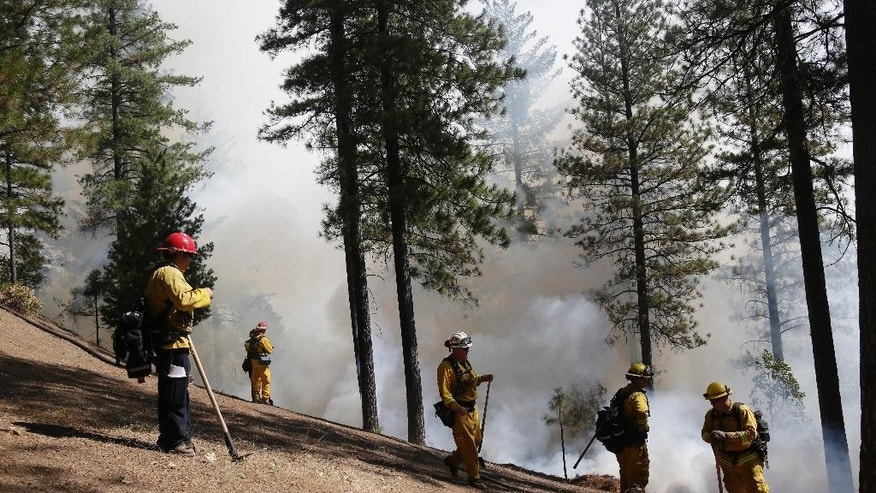 Firefighters hold the line along a containment area while fighting the King Fire on Tuesday, Sept. 23, 2014, in Mosquito, Calif. Strike teams from Fresno and El Dorado Cal Fire worked in conjunction with department of corrections crews in an offensive firing tactic, intended to take away fuel from the main fire. Nearly 2,000 firefighters were added Tuesday to battle the massive wildfire threatening thousands of homes, in anticipation of erratic winds and hotter temperatures that could undo their progress.  (AP Photo/Marcio Jose Sanchez)