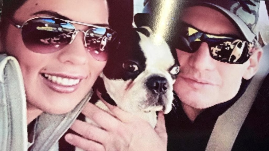 In this undated photo released by Erica Carmichael, Brian Callans, right,  poses for a photo with his fiancée Erica Carmichael, and their dog Bob in Alabama. Callans, 46, of Birmingham, and driver supervisor Doug Hutcheson, 33, of Odenville, were the men killed Tuesday, Sept. 24, 2014, in at a Birmingham, Ala., UPS facility. (AP Photo/Erica Carmichael)