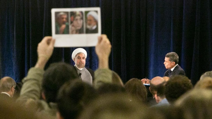 Iran's President Hassan Rouhani, left, looks at a protester holding a picture who interrupted while he was speaking at New America, a public policy institute and think tank, on Wednesday, Sept. 24, 2014 in New York.  Protesters say the individuals in the picture are all dissidents under house arrest in Iran and called on the President Rouhani to facilitate their release.  (AP Photo/Bebeto Matthews)