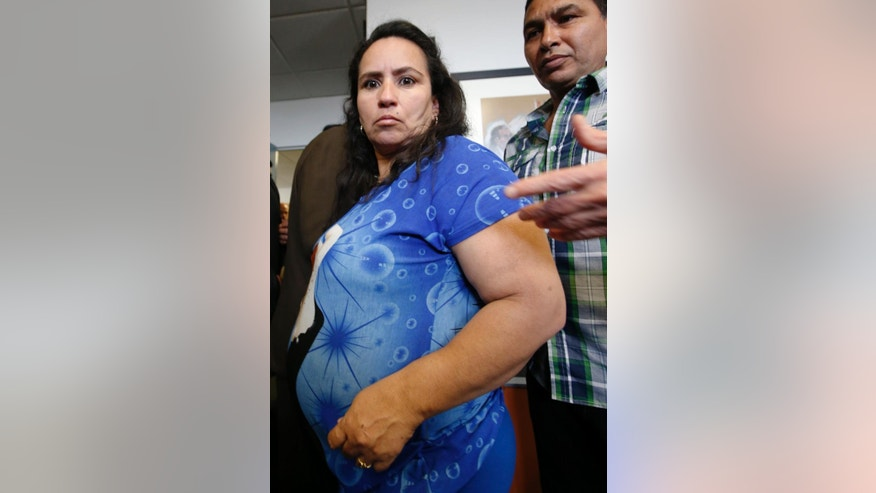 Sandra Amezquita, 43, who is 5 months pregnant, along wiht her husband Ronel Lemos, leave a press conference at the offices of her attorney Wednesday, Sept. 24, 2014, in New York. Amezquita, who was caught on amateur video showing a New York police officer taking her to the ground on her stomach as she tried to intervene in the arrest of her 17-year-old son early Saturday morning, Sept. 20, in Brooklyn, and a woman who says she tried to come to Amezquita's aid, have requested a criminal investigation regarding the officer's actions.  (AP Photo/Kathy Willens)