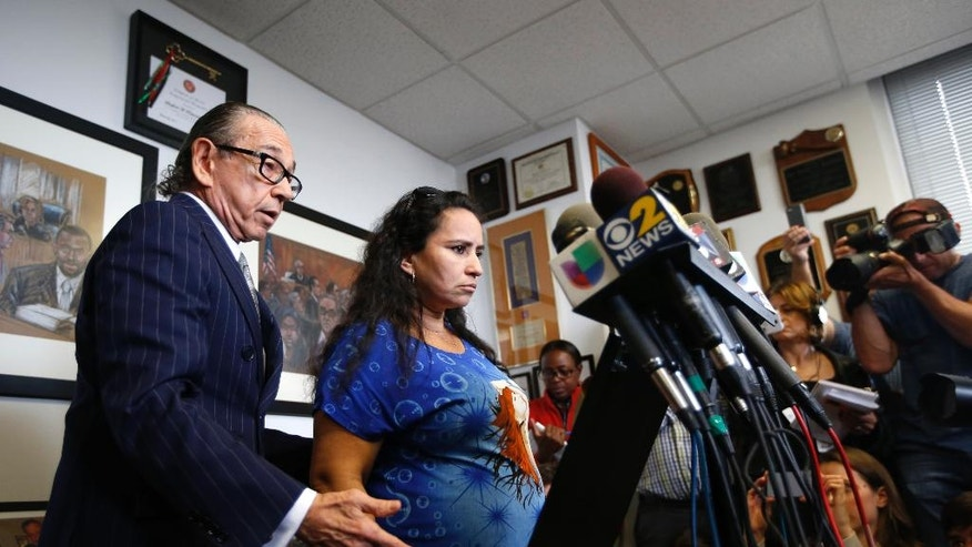 Attorney Sanford A. Rubenstein, left,  introduces client Sandra Amezquita, 43, who is 5 months pregnant, during a press conference at his offices in New York, Wednesday, Sept. 24, 2014. Amezquita, who was caught on amateur video showing a New York police officer taking her to the ground on her stomach as she tried to intervene in the arrest of her 17-year-old son early Saturday morning, Sept. 20, in Brooklyn, and a woman who says she tried to come to Amezquita's aid, have requested a criminal investigation regarding the officer's actions.  (AP Photo/Kathy Willens)