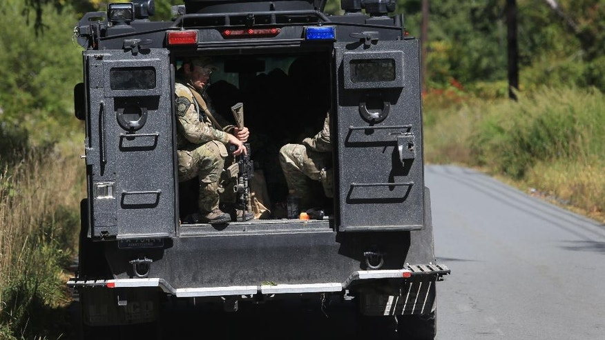 Pennsylvania State Police troopers ride in a tactical vehicle to help create a perimeter in the search area for Eric Frein near Canadensis, Pa., on Tuesday, Sept 23, 2014. The manhunt for the survivalist accused of ambushing a state police barracks has narrowed to the rural area where he grew up and his parents still live, but Frein, the suspect, has managed to elude capture despite the efforts of hundreds of law enforcement officials.  (AP Photo/The Times-Tribune, Jake Danna Stevens)WILKES BARRE TIMES-LEADER OUT; MANDATORY CREDIT