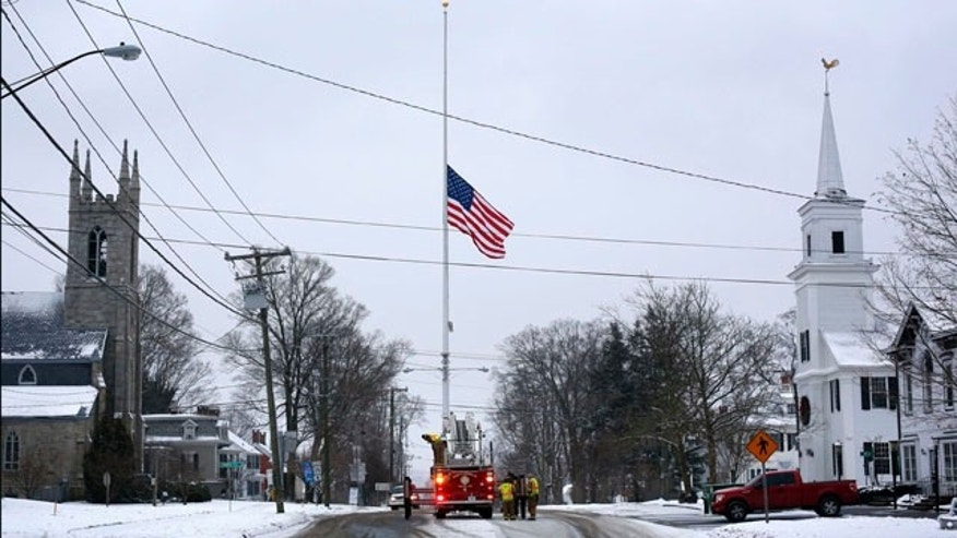 December 14, 2013: On the first anniversary of the Sandy Hook massacre, firefighters in Newtown, Conn. lower the town's flag on Main Street to half-staff in honor of the victims. (AP Photo/Robert F. Bukaty, File)