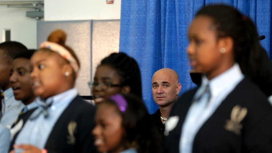 Hall of Fame tennis player Andre Agassi, center rear, looks on as students perform during an assembly at University Heights Charter School, Wednesday, Sept. 24, 2014, in Newark, N.J.  Agassi and Bobby Turner, who have teamed up to build the Turner-Agassi Charter School Facilities Fund to help create schools, were given a tour of the once button factory that now serves as a school for children from kindergarten to eighth grade. (AP Photo/Julio Cortez)