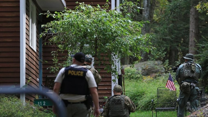 Pennsylvania State Police troopers and U.S. Marshals investigate and clear homes in the search for suspect Eric Frein, Wednesday, Sept. 24, 2014 in Canadensis, Pa.  Frein, a suspect in the fatal ambush of a trooper has occasionally made himself visible to officers before melting back into the forest, and police found empty packs of Serbian-branded cigarettes and soiled diapers believed to have been left by him, Pennsylvania State Police said Wednesday.   (AP Photo/The Times-Tribune, Jake Danna Stevens)  WILKES BARRE TIMES-LEADER OUT; MANDATORY CREDIT