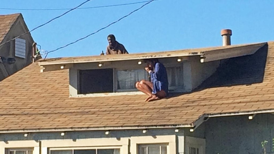 In this Wednesday, Sept. 24, 2014 photo, Laura Rivera, who fled her house through an attic window to escape an intruder, seen on the roof behind her, waits for help after an early-morning break in at her house in the Venice neighborhood of Los Angeles. The intruder, later identified as Christian Hicks, was arrested by Los Angeles police officers and is being held for investigation of burglary. (AP Photo/Venice311.org, Alex Thompson) MANDATORY CREDIT