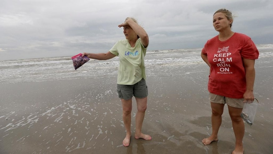 Jill Howard, left, and her stepdaughter Martie Belt, talk about the arrest of Leroy Matthew Jr. as they walk along the beach Thursday, Sept. 25, 2014, near Gilchrist, Texas, on the Bolivar Peninsula. Matthew Jr. was arrested on a beach in the Texas community of Gilchrist by Galveston County Sheriff's authorities, Charlottesville Police Chief Timothy Longo announced Wednesday night Sept. 24, 2014. He is charged with abducting missing University of Virginia sophomore Hannah Graham and is awaiting extradition. (AP Photo/David J. Phillip)