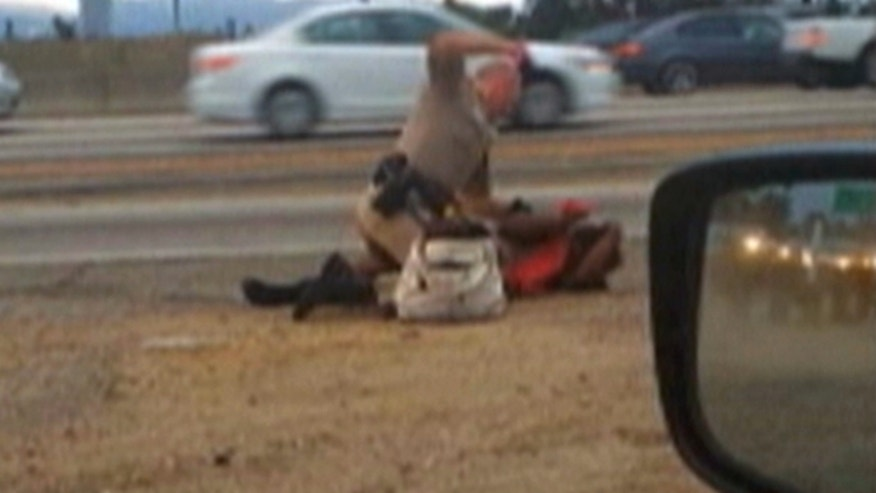 July 1, 2014: In this image made from video provided by motorist David Diaz, a California Highway Patrol Officer David Andrew straddles a woman identified as 51-year-old Marlene Pinnock while punching her in the head on the shoulder of a Los Angeles freeway. (AP)