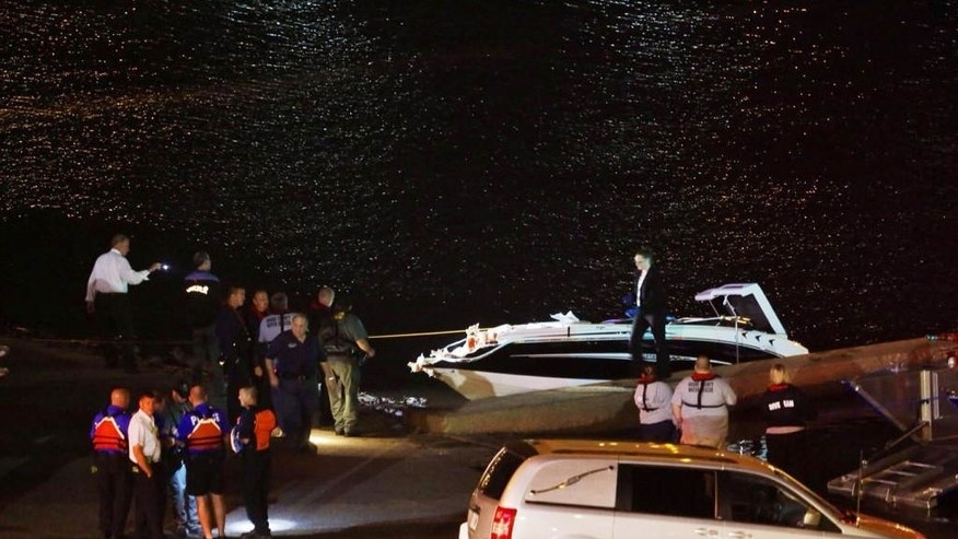 Emergency personnel and investigators gather by the Ohio River on Thursday night, Sept. 25, 2014  after an accident near Cincinnati. Two off-duty FBI employees were killed in a collision between a barge and a boat on the Ohio River the agency said Friday. Cincinnati District Fire Chief Lou Arnold said the accident happened late Thursday when the men's pleasure boat hit a 600-foot barge in the river between Cincinnati and Newport, Kentucky. The two were found dead on the boat when fire crews arrived, authorities said. (AP Photo/The Cincinnati Enquirer, Carrie Cochran)  MANDATORY CREDIT;  NO SALES
