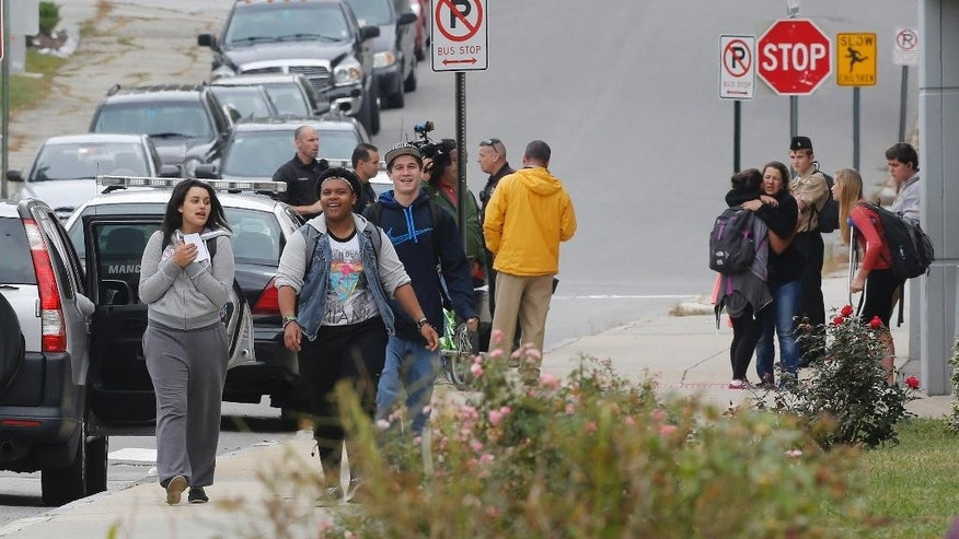 Students gather outside Manchester West High School after a 90-minute lockdown was released Thursday Sept. 25, 2014 in Manchester, N.H. Police arrested Damian Johnson, 21, a former student after he showed up in a classroom with a pellet gun in his waistband.(AP Photo/Jim Cole)