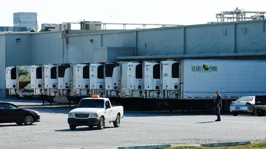 Trucks are parked in a parking lot at Vaughn Foods in Moore, Okla., Friday, Sept. 26, 2014, the site of an incident where a man beheaded a woman with a knife and was attacking another worker when he was shot and wounded by a company official, on Thursday. (AP Photo/Sue Ogrocki)