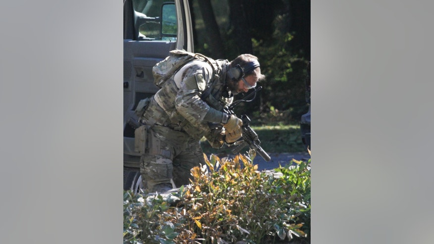 An FBI agent clears his weapon after exiting a wooded area at Buck Hill Falls in Barrett Township, Pa, where the search for Eric Frein continues Friday, Sept 26, 2014. Frein is suspected of fatally shooting a state trooper and wounding another at the Blooming Grove state police barracks two weeks ago. (AP Photo/Scranton Times & Tribune, Michael J. Mullen)