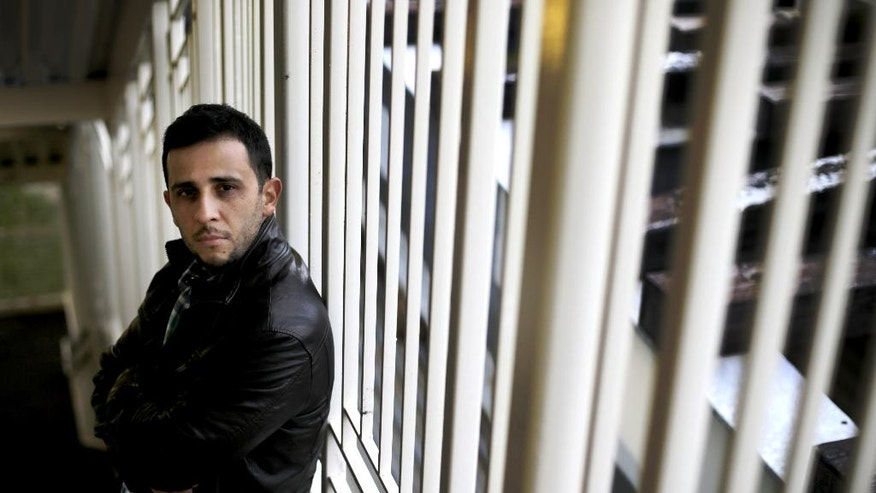 "In this Sept. 21, 2014, photo, Angel Herrera poses for portrait on a Chicago Transit Authority train station near his boyhood home in Chicago. Herrera, who served in Iraq, said he was forced to confront the wrong-headed decisions he'd made as a teen where he used drugs, hung out with and admired the wrong people, including an uncle who was a gang member. For years, he said, he shut himself off from that past. ""I put that kid away. I hated him. I was ashamed of the person I was,"" said Herrera. By talking with the kids, even admitting he had some negative first impressions of them, he said he understood himself better. (AP Photo/Charles Rex Arbogast)"