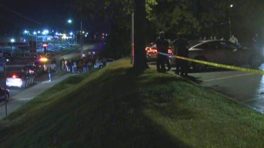 In this framegrab image courtesy of KSDK-TV police watch, right, as a crowd gathers near the scene where a police officer was shot in the arm Saturday night Sept. 27, 2014 in Ferguson, Missouri. The officer was shot in the arm and is expected to survive, St. Louis County Police Chief Jon Belmar said. (AP Photo/KSDK-TV)