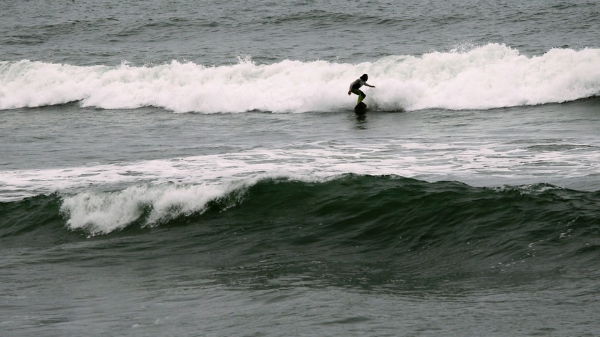 Surfer Joao Demacedo rides a wave at Martin's Beach, a popular surfing and fishing spot, in Half Moon Bay, California.
