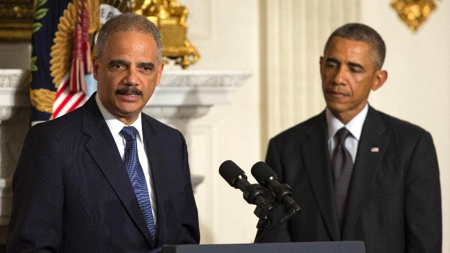 President Barack Obama, right, looks on as Attorney General Eric Holder speaks in the State Dining Room of the White House, on Thursday, Sept. 25, 2014, in Washington. Holder, who served as the public face of the Obama administration's legal fight against terrorism and weighed in on issues of racial fairness, is resigning after six years on the job. He is the first black U.S.  attorney general. (AP Photo/Evan Vucci)