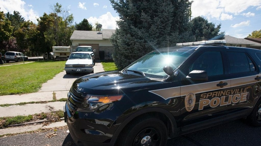 A police vehicle sits outside of 954 East 900 South in Springville Sunday, Sept. 28, 2014, where a family of five was found dead the night before. (AP Photo/The Deseret News, Laura Seitz)