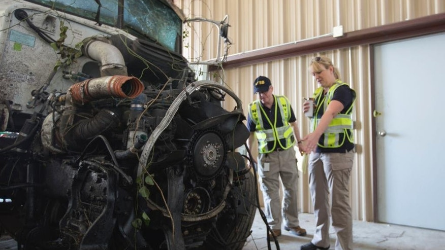 In this photo provided by The National Transportation Safety Board, officials examine part of the wreckage involved in a fatal highway accident in Davis, Okla. The collision late Friday badly damaged the driver's side of the North Central Texas College Softball team bus driven by a coach with 15 players aboard as they returned from a scrimmage against Southern Nazarene University in Bethany, Okla. Four women's softball players were killed. (AP Photo/National Transportation Safety Board)