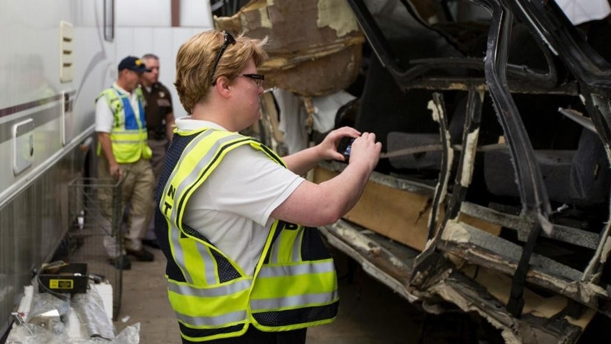 In this photo provided by The National Transportation Safety Board, Mary Pat McKay documents part of the wreckage involved in a fatal highway accident in Davis, Okla. The collision late Friday badly damaged the driver's side of the North Central Texas College Softball team bus driven by a coach with 15 players aboard as they returned from a scrimmage against Southern Nazarene University in Bethany, Okla. Four women's softball players were killed. (AP Photo/National Transportation Safety Board)