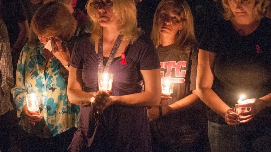 Doris Floyd, from left, Sherry Smith, Wendy Perkins and Susan Decker attend at a candlelight vigil at North Central Texas College in Gainesville, Texas, Sunday, Sept. 28, 2014, for four members of the school softball team who were killed Friday in a highway collision while returning from a scrimmage game in Oklahoma. The Oklahoma Highway Patrol identified the four players killed as Meagan Richardson, Brooke Deckard, Katelynn Woodlee and Jaiden Pelton. All were from North Texas. (AP Photo/Rex C. Curry)