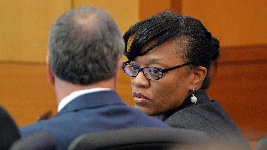 Defendant Dana Evans talks to her attorney, Robert Rubin, during the prosecution's opening statement in a case against 12 former Atlanta Public Schools educators and administrators, in Atlanta, Monday, Sept. 29, 2014 in Fulton County Superior Court. Prosecutors said 12 former Atlanta Public Schools educators and administrators cheated, lied and stole as part of a widespread but cleverly disguised conspiracy to inflate state test scores that affected thousands of students. Prosecutors have agreed to plea deals with 21 other defendants included in the initial indictment. (AP Photo/Atlanta Journal-Constitution, Kent D. Johnson, Pool)