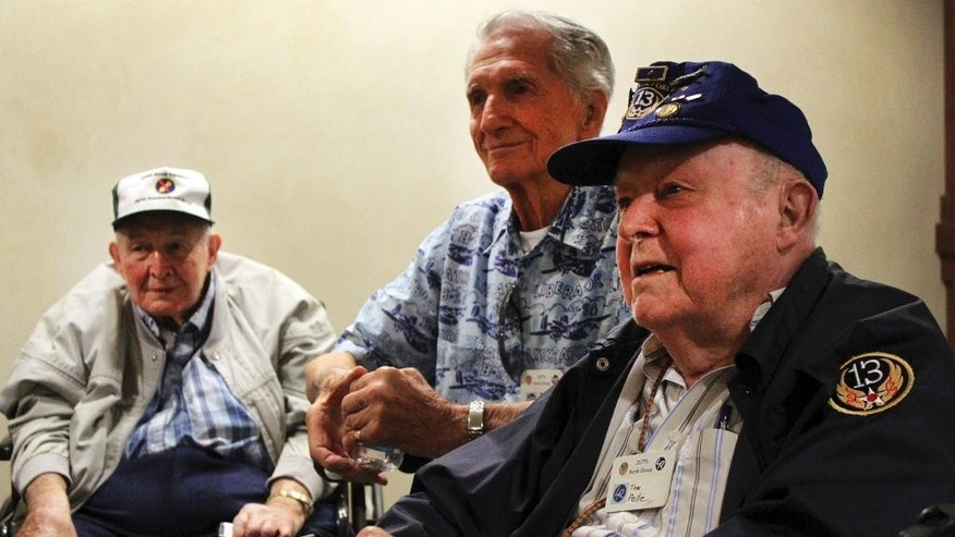In this Sept. 18, 2014 photo, World War II veterans, from left, Earl McGuire, Jack Palmer and Tom Pelle talk about their service with the 307th Bombardment Group during a reunion in Santa Fe, N.M. Pelle and the few other remaining members of the 13th Air Force's famous 307th Bombardment Group, their family members and Ancestry.com's military records site Fold3 are working to keep alive the group's memory by collecting and digitizing thousands of photographs, military orders and other memorabilia. The records are being posted online as part of a searchable database. (AP Photo/Susan Montoya Bryan)