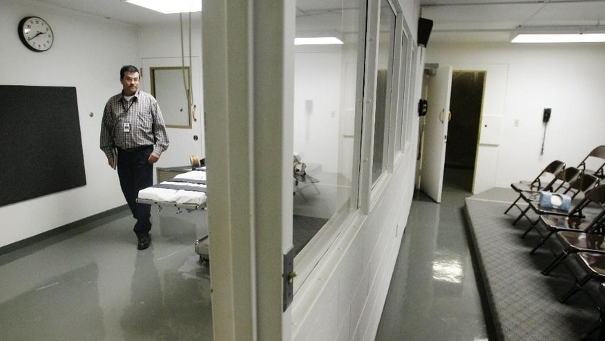 FILE - In this April 15, 2008 file photo, Terry Crenshaw, wardens assistant at the Oklahoma State Penitentiary, walks past the gurney in the execution chamber at left, in McAlester, Okla. At right are the rows of chairs in which witnesses to executions are seated. Oklahoma prison officials are unveiling new execution protocols to replace those used when an inmate took 43 minutes to die last spring. (AP Photo, file)