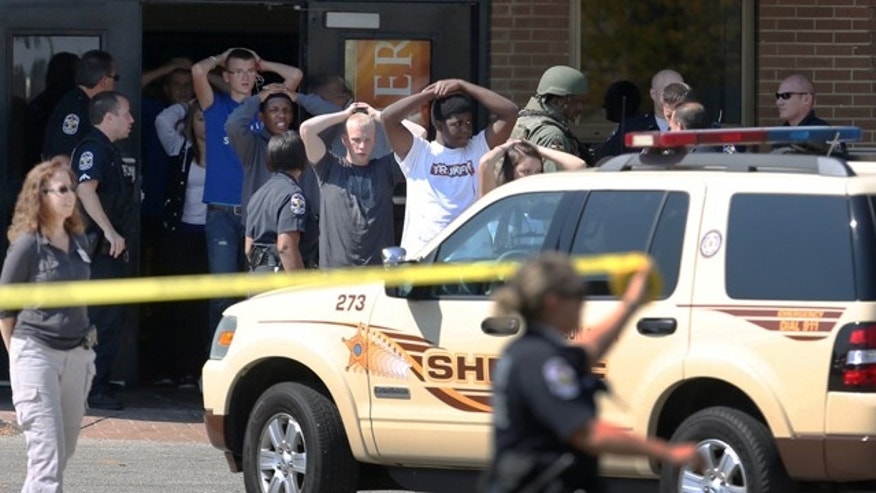 September 30, 2014: Students put their hands on their heads as they are led out of Fern Creek High School in Louisville, Ky. (AP Photo/The Courier-Journal, Scott Utterback)
