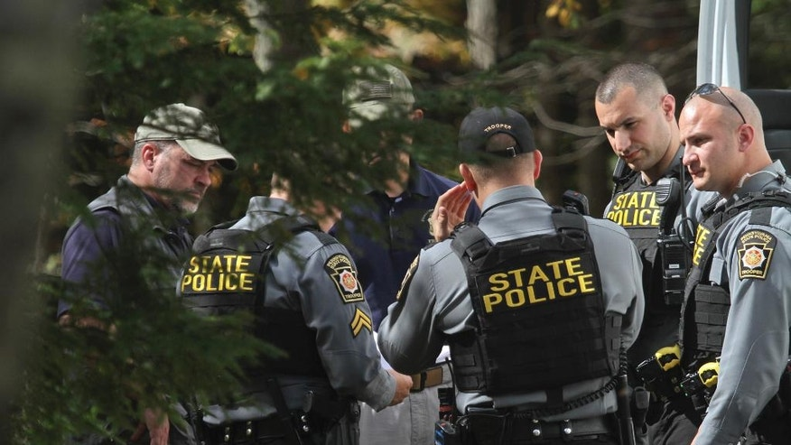 Pennsylvania State Police confer along Snow Hill Road in Price Township, Pa, Tuesday, Sept. 30, 2014 as the search for suspected killer Eric Frein carries on for the 18th day. State police searching for Frein, accused of killing a trooper, said Tuesday they found two pipe bombs in the Pennsylvania woods during their manhunt that were capable of causing significant damage. The bombs were not deployed, but they were fully functional and had both trip wires and fuses, Lt. Col. George Bivens said at a news conference.  (AP Photo/Scranton Times-Tribune, Michael J. Mullen) MANDATORY CREDIT