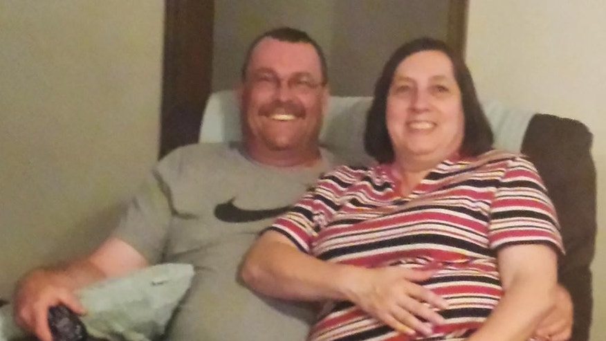 In this undated photo provided by the Hufford family, Colleen Hufford, right, is pictured with her husband, K.C. Hufford, relaxing in their home in Moore, Okla. Colleen Hufford was recently slain during a workplace incident at Vaughan Foods in Moore, Okla. (AP Photo/Courtesy Hufford Family)