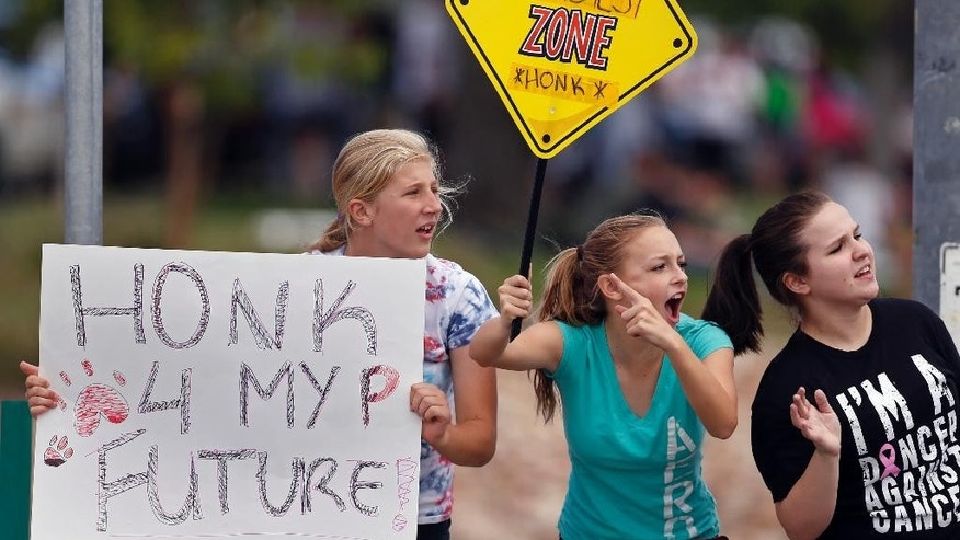 In this Sept. 23, 2014 photo, protesting Pamona High School students, left to right, Ciana Vrtikapa, Tori Suyak, and Becca Ferris engage with passing motorists in a busy intersection near their school, during a multi-school protest against a Jefferson County School Board proposal to emphasize patriotism and downplay civil unrest in the teaching of U.S. history, in Arvada, Colo. (AP Photo/Brennan Linsley)
