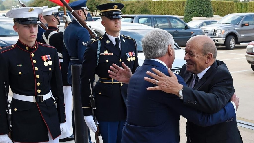 Defense Secretary Chuck Hagel greets French Defense Minister Jean-Yves Le Drian as he arrive for an honor cordon at the Pentagon, Thursday, Oct. 2, 2014. (AP Photo/Susan Walsh)